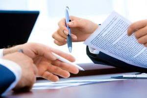 Two peoples' hands holding pens and paper