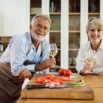 Older couple drinking wine in kitchen