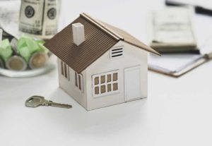 Model of a home next to a key and money