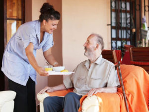 Woman-Handing-a-Food-Tray-to-Older-Main-in-Chair